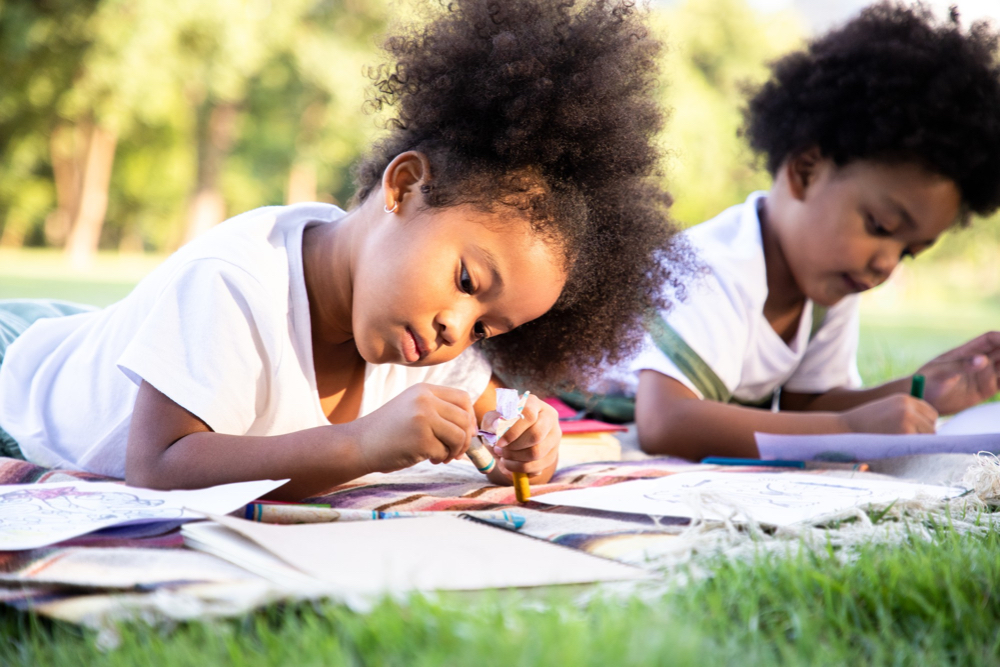 african american girl and boy are outside on the grass laying on the grass using their imagination to draw art