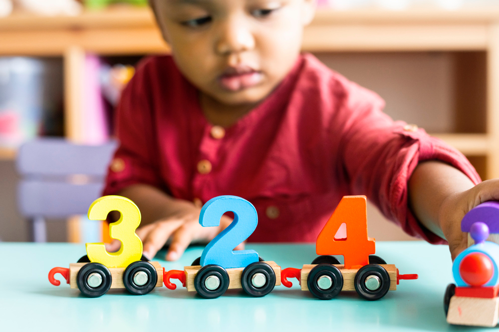 little african american boy playing with wooden mathematics toy nursery